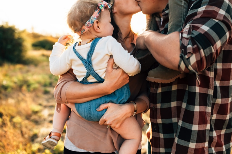 Salt Lake City Birth and Family Photography, couple kissing with toddler in mom's arms