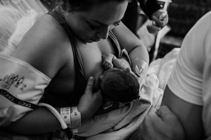 Salt Lake City Birth and Family Photography, black and white of mother letting new baby try breastfeeding