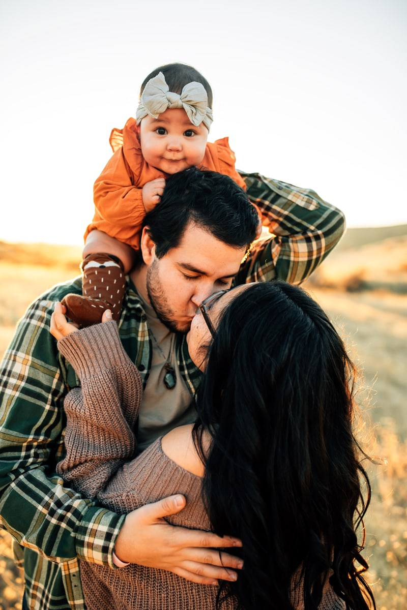 Salt Lake City Birth and Family Photography, couple kissing with baby sitting on father's shoulders